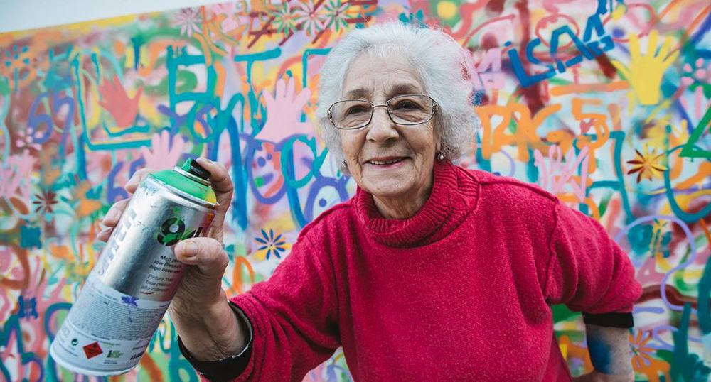 An older woman with white hair, wearing a red sweater, holding a spray paint can.