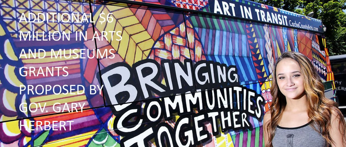 """A brown haired woman stands in front of a wall that reads, """"Bringing Communities Together."""""""