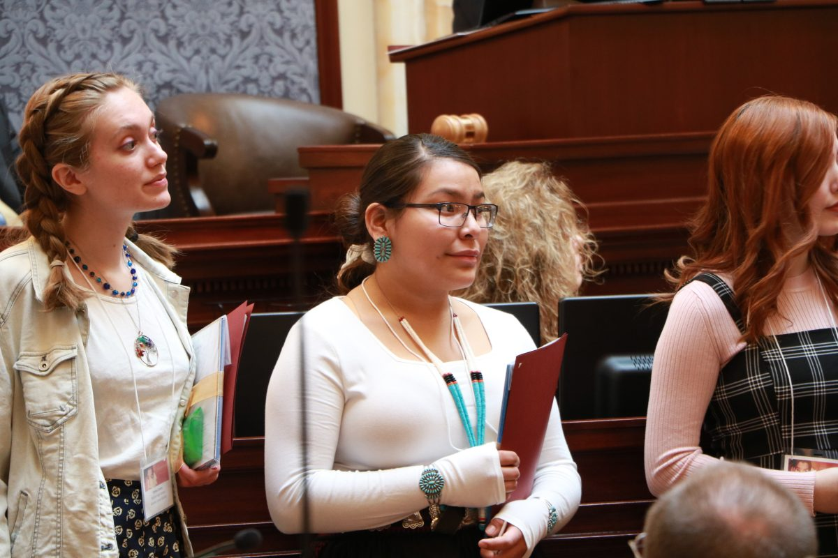 Three young people standing on the Utah Senate floor holding folders.