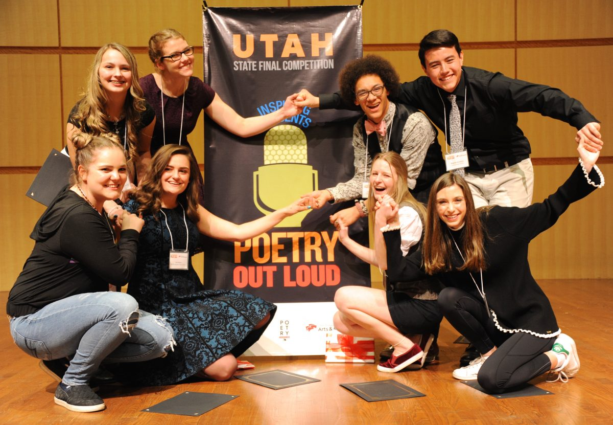 A group of students posing in front of a Poetry Out Loud banner.