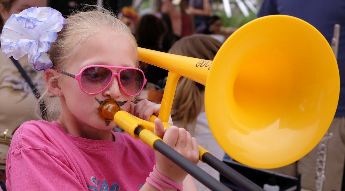 A girl wearing pink glasses playing a plastic, yellow trombone.