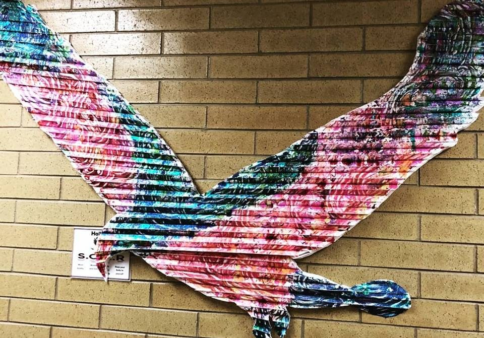 An image of a colorful eagle on a brick wall.