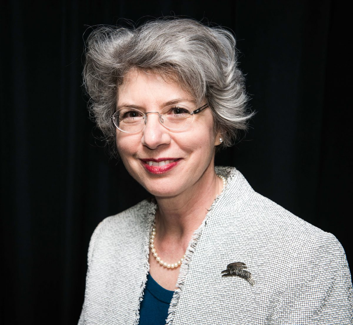 Portrait of a woman with grey hair smiling, wearing glasses and a grey blazer.