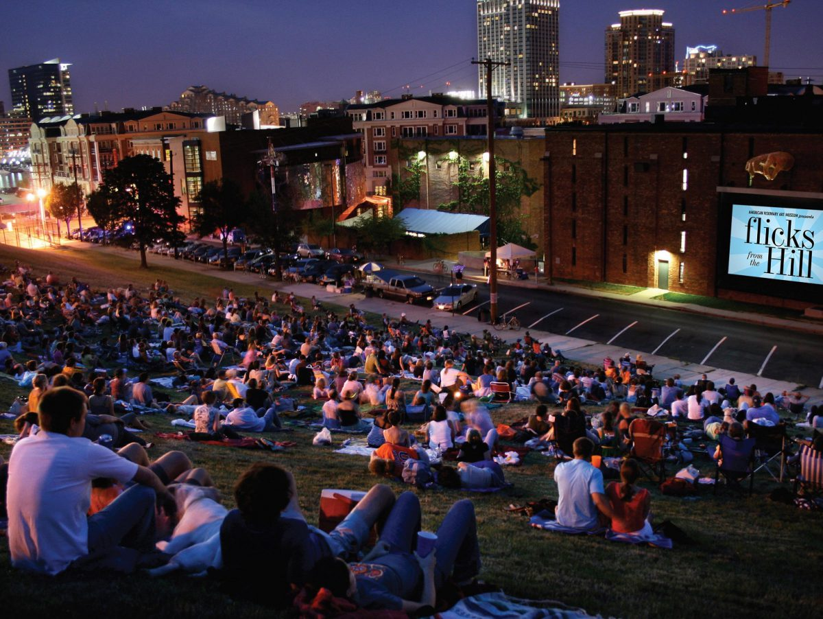 People in a city sit on blankets in a park and watch an outdoor film.