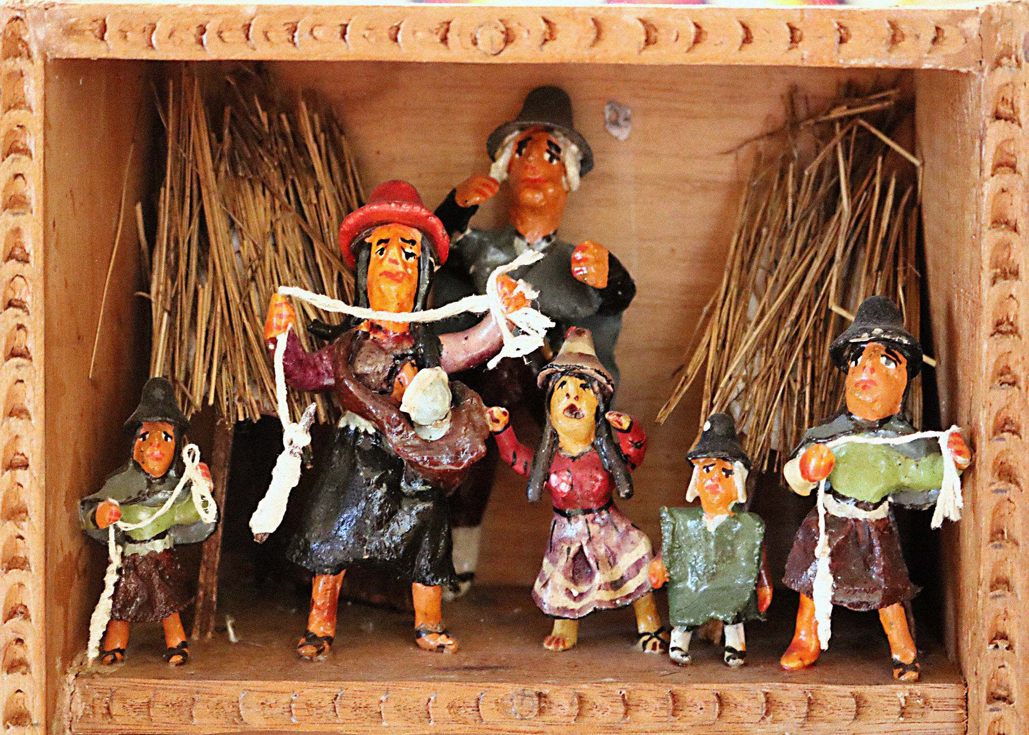 A scene called The Uchuraccaynos within a retablo. The scene portray a family of humanlike figurines. There are two, taller adults and four shorter children. There is also a baby strapped to one of the adults. One of the adults and two children hold white ropes. There are looks of anguish and sadness of all of their faces. The figurines stand between two structures with straw roofs.