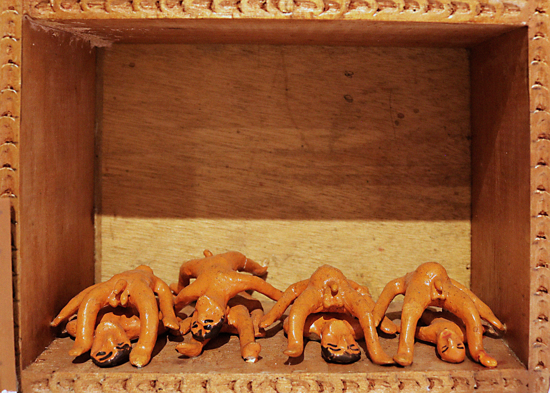 A scene called The Burial within a retablo. Four humanlike figurines lay on the base with four addition naked, humanlike figurines standing in a crab-walk position above them.
