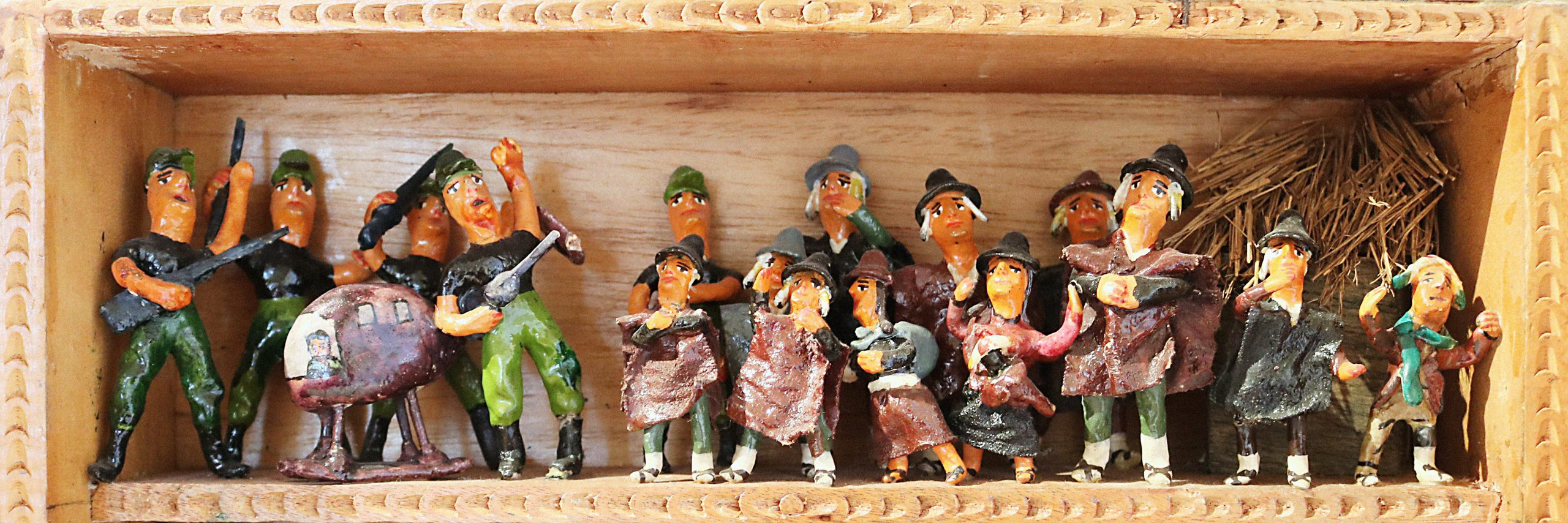 A scene called Helicopter and Commoners within a retablo. The scene portrays two groups of humanlike figurines. On the left are four men dressed in military-like uniforms, holding guns. These men stand by a helicopter with a pilot seen inside. On the left is a group of commons wearing ponchos and hats with looks of worry on their faces. The commoners stand in from of what appears to be a structure with a straw roof.