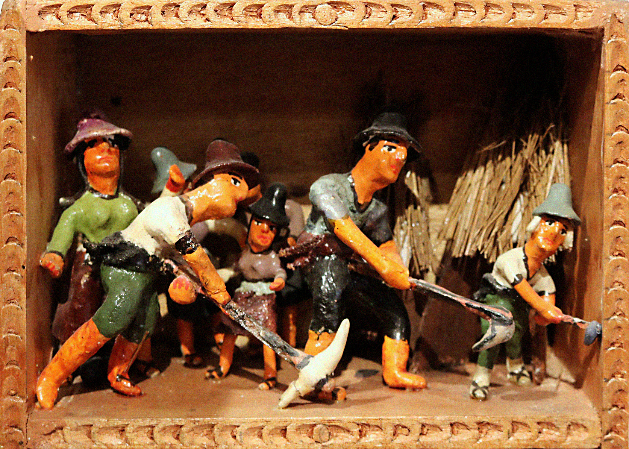 A scene called Sowing within a retablo. The scene portrays humanlike figurines wearing hats and holding farming tools, as though they are working in a field. In the backgroup are what appear to be structures with straw roofs.