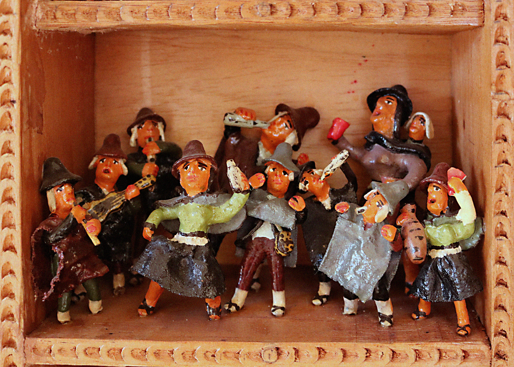 A scene called Traditional Customs within a retablo. The scene portrays humanlike figurines in a group. The men and women portrayed wear earthy colors like green, grey, brown, and dark red. All the figurines wear hats. Most hold and drink from white bottles. One figurine holds a guitar and two other hold flutes to their mouths.