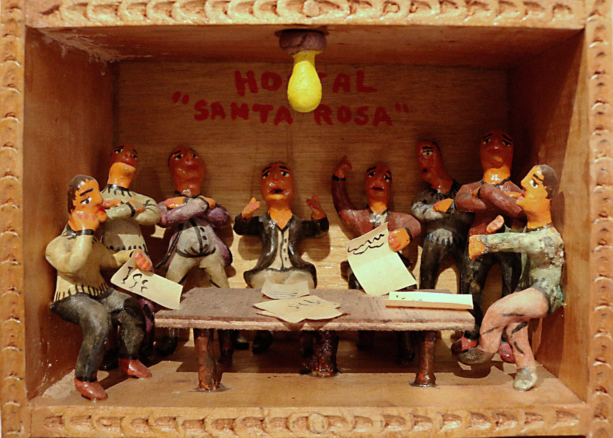 A scene called Reunion within a retablo. The scene portrays eight men gathered around a table. There are papers scattered on the table and two men hold papers. All the men have looks of anguish or sadness on their faces.