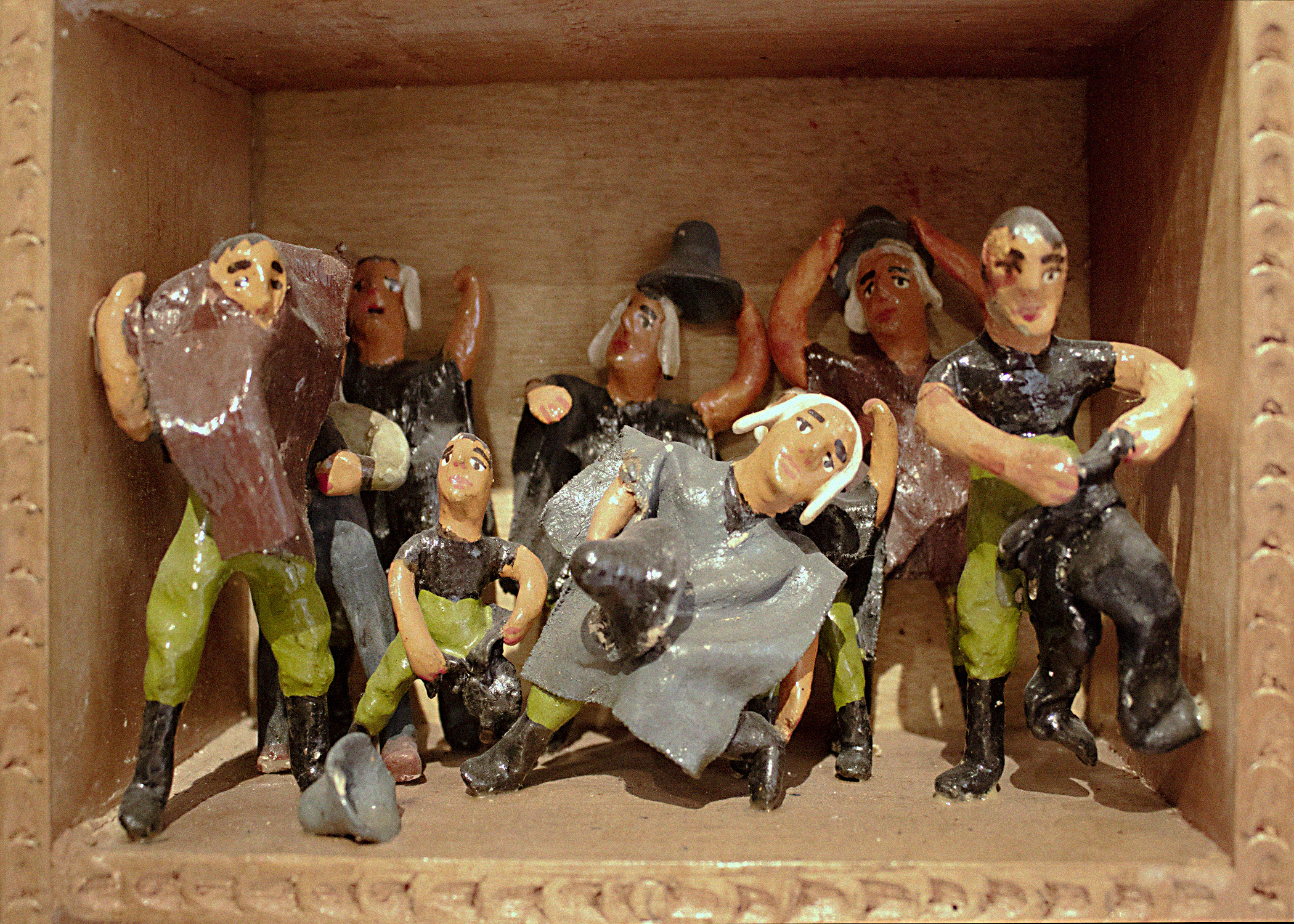A scene called Disguise within a retablo. A group of nine humanlike figurines are portrayed as dressing themselves in grey and brown ponchos and grey hats.