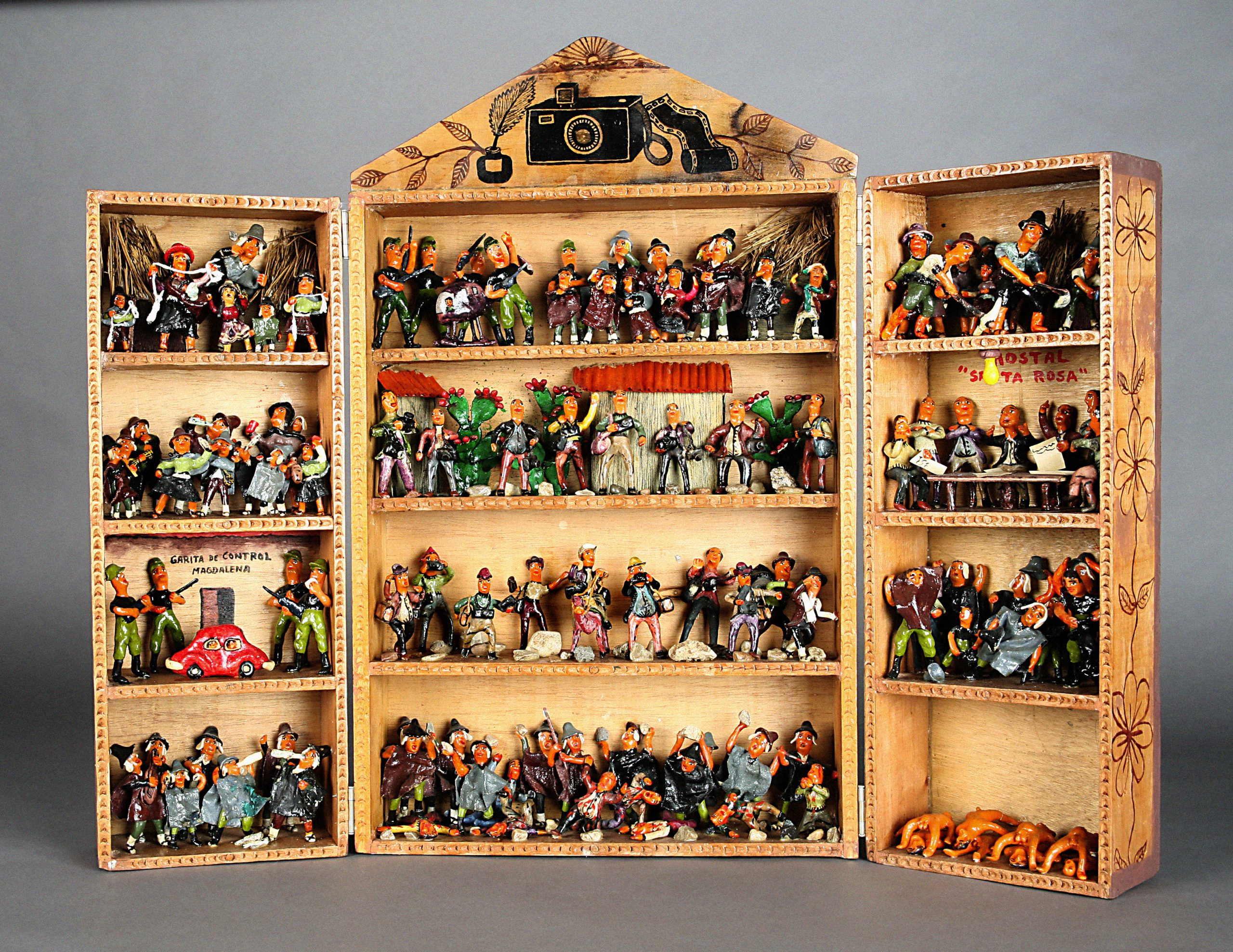 An image of a retablo. The retablo has a likeness to an open cabinet with shelves, each containing figurines portraying different scenes.