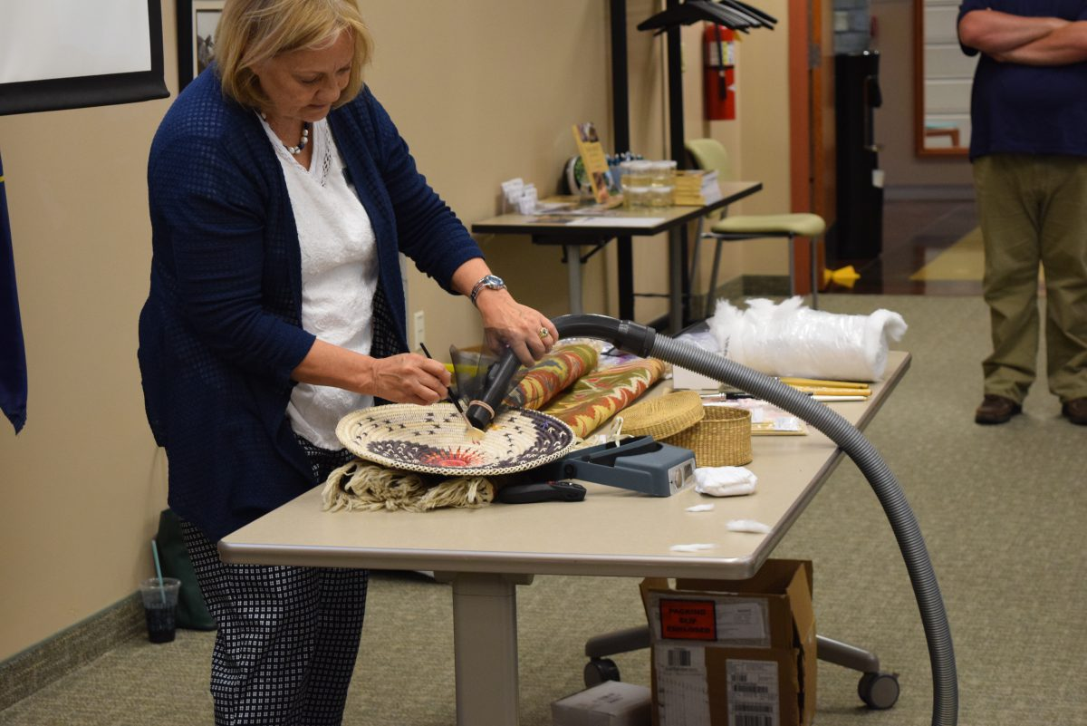 A blonde woman in a blue cardigan cleans a Navajo basket in a collections care workshop.