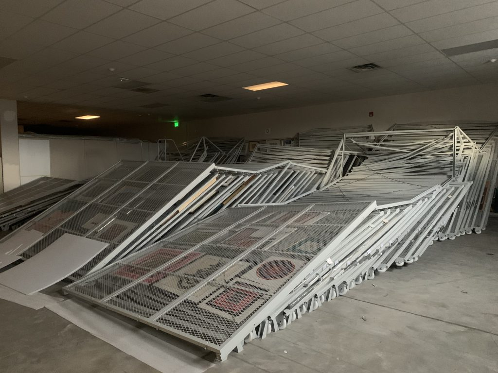 Racks of art storage shelving is toppled over in a large storage room.
