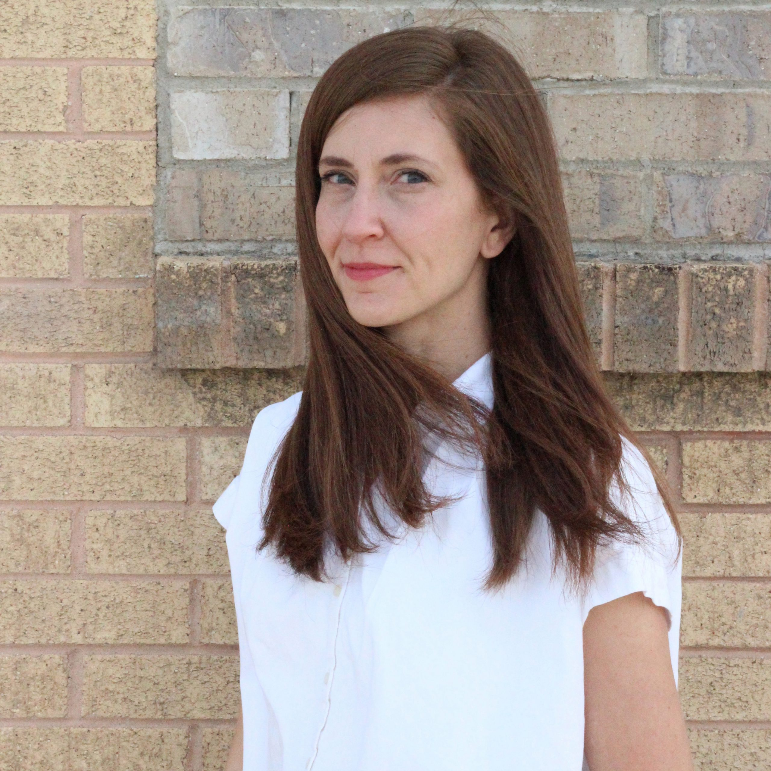 A photo fo a white woman with brown hair standing in front of a brown brick wall.