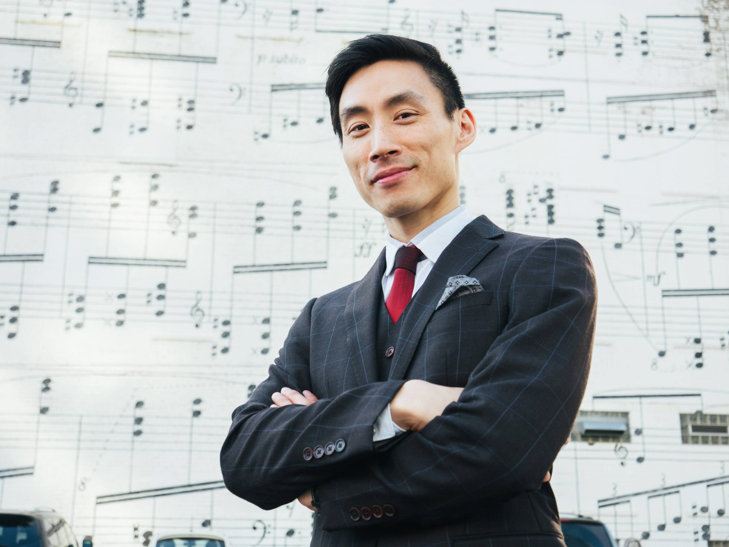 An Asian man wearing a suit standing with his arms crossed in front of a wall with sheet music.