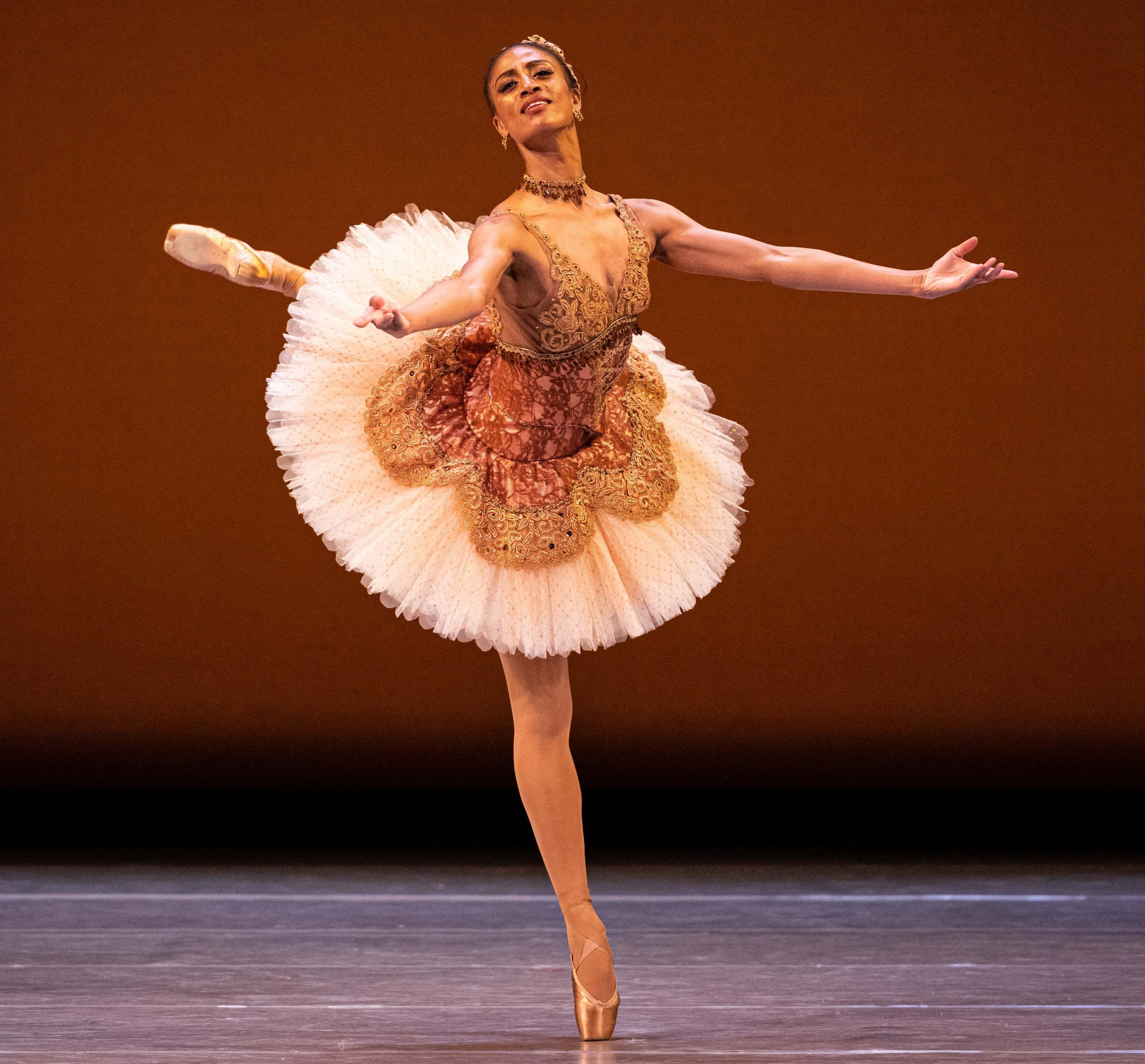 A photo of a female ballerina balancing on a single foot on pointe.