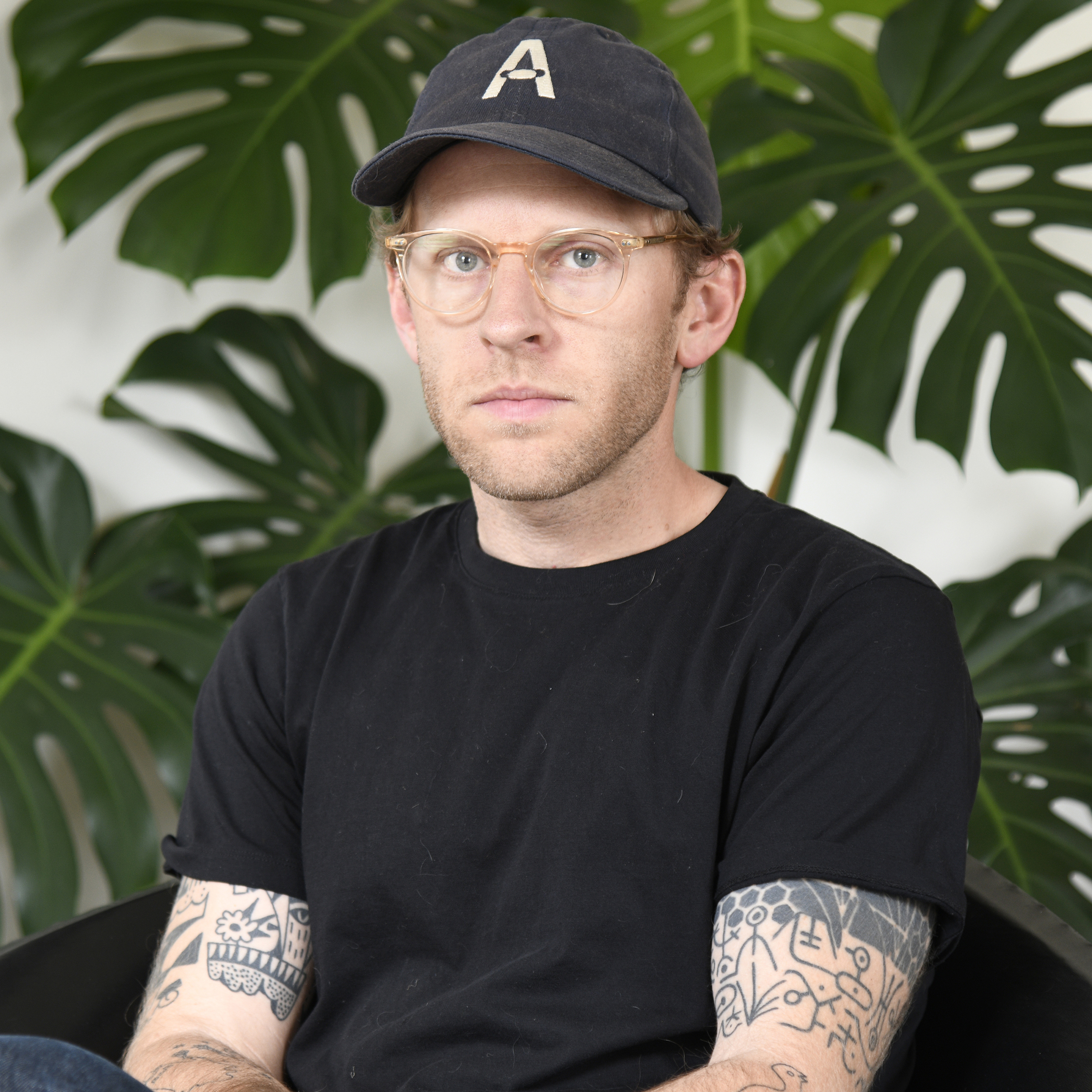 A photo of a white man wearing glasses, a black hat, and a black shirt.