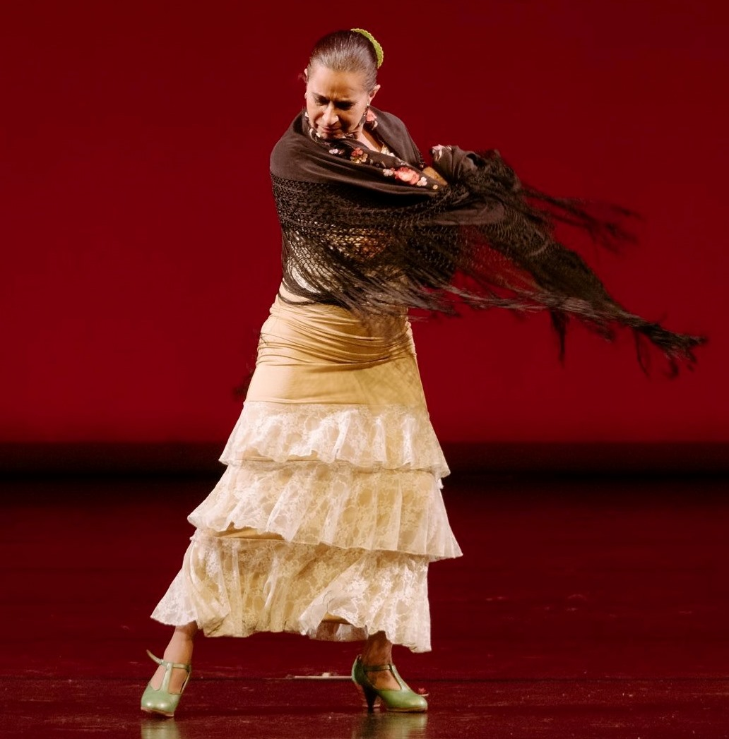A photo of a woman wearing a white ruffled dress and a brown shawl dancing on a stage with a red background.