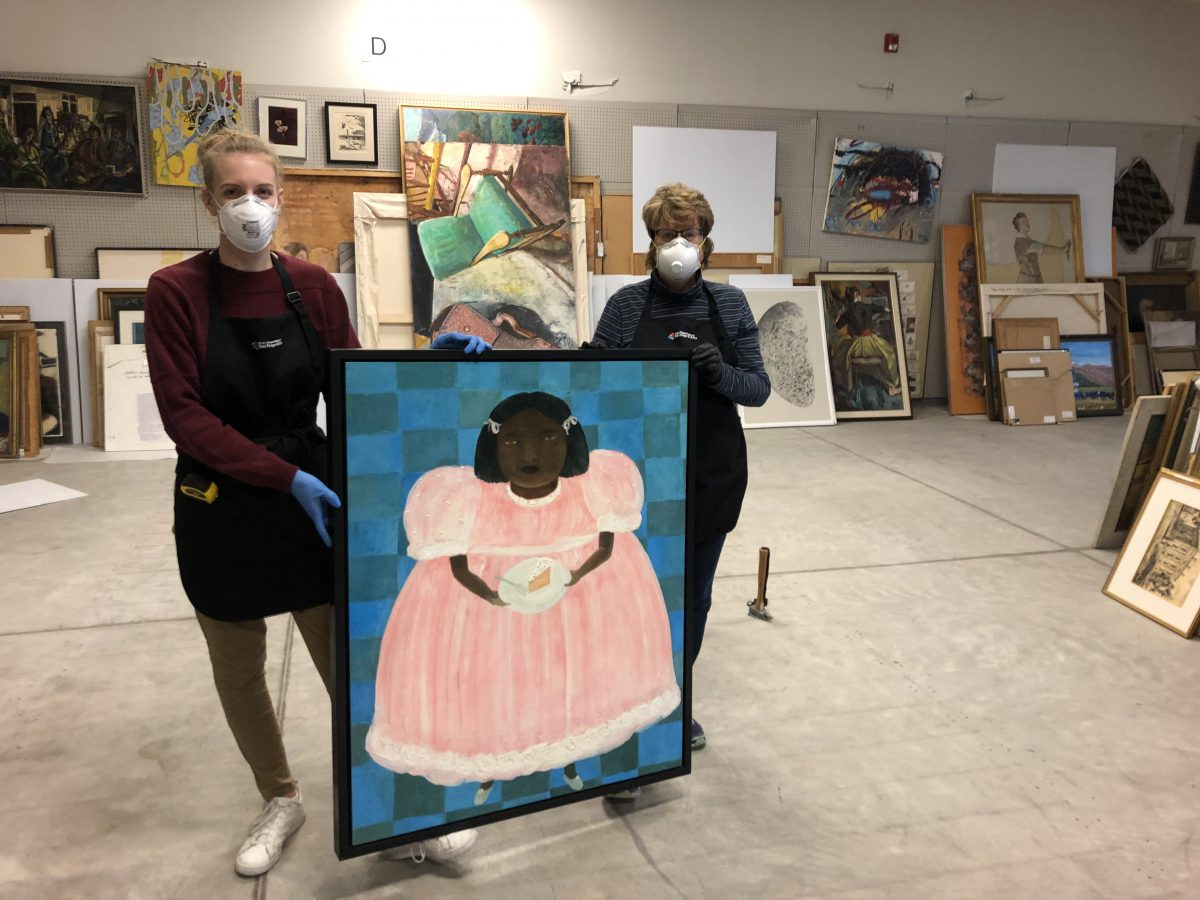Two women wearing black aprons and white face masks stand in an art storage facility holding a painting of a young brown-skinned girl in a pink dress with a piece of cake.