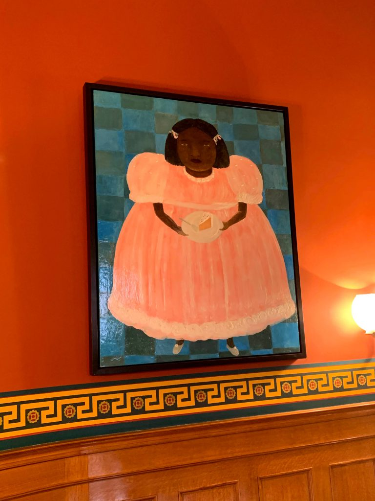A painting of a young brown-skinned girl in a pink dress with a piece of cake hangs on an orange wall.