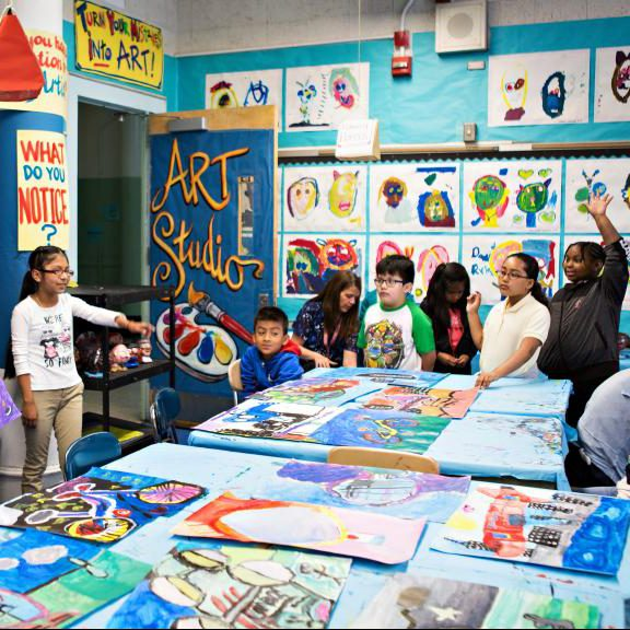 A group of young students gather around a table in a colorful classroom with art on the walls.