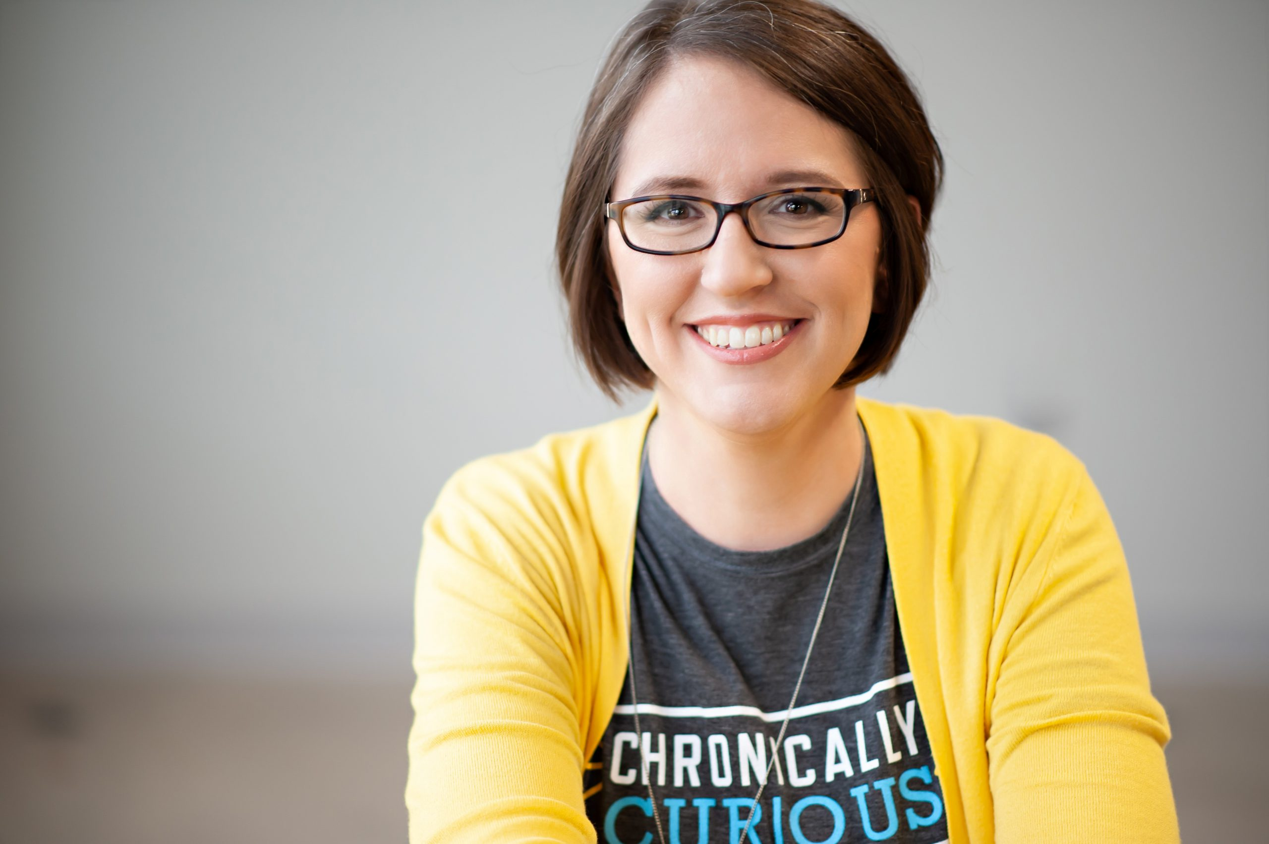 A photo of a white woman wearing glasses and a yellow cardigan.