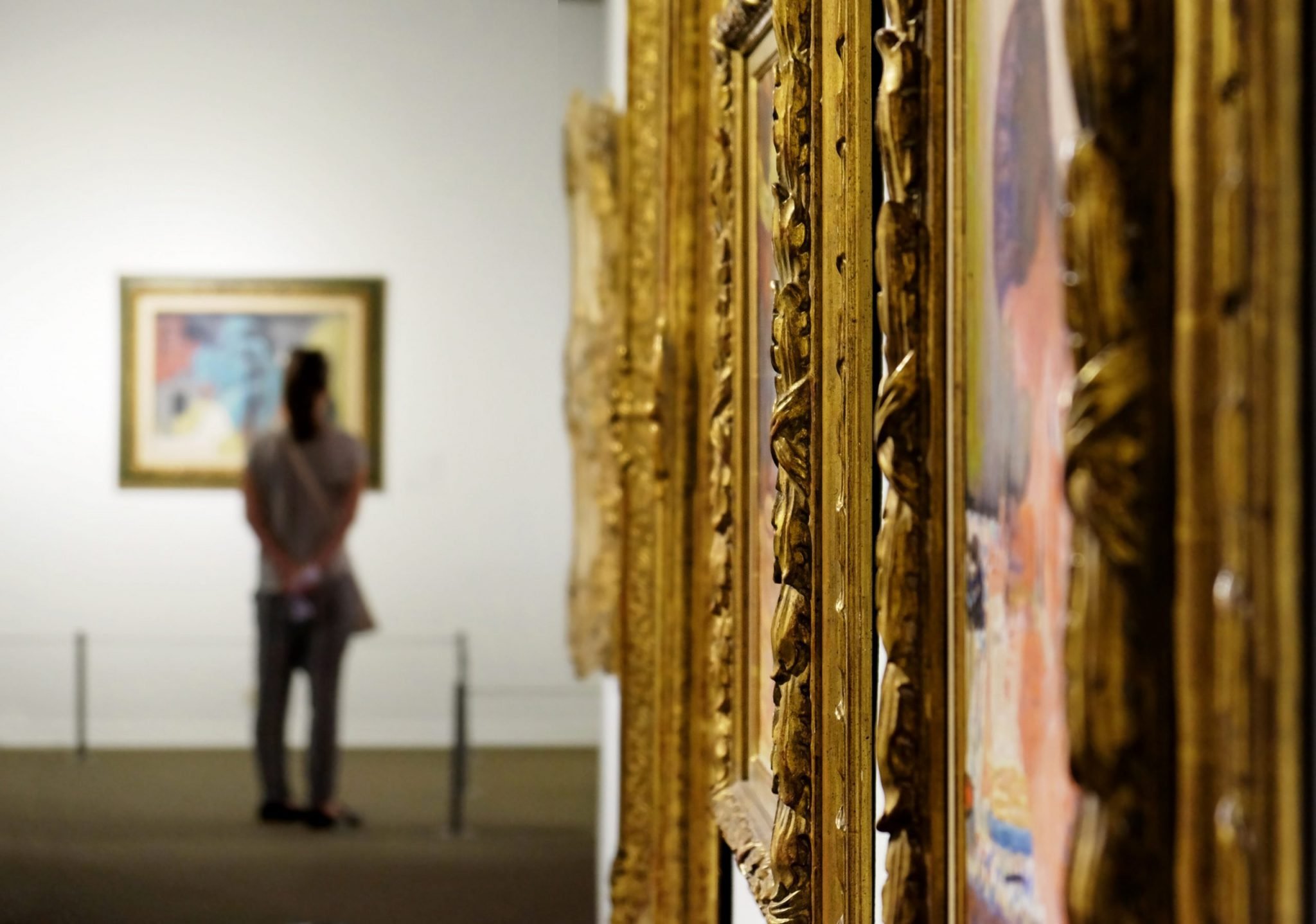 Golden, ornate frames in an art gallery with a person standing in the distance.