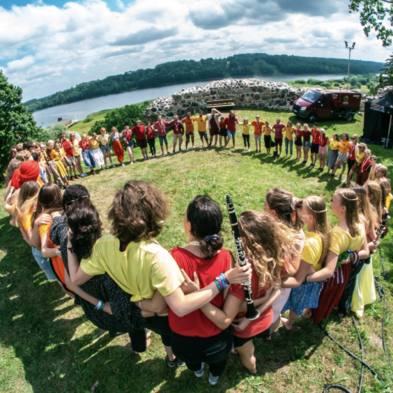 A group of young people standing on grass in a circle.